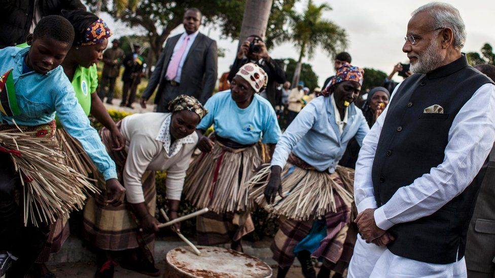 Indian Prime Minister Narendra Modi (R) looks at a band playing, as he arrives for a visit to the Centre for Innovation and Technological Development on 7 July 2016 in Maputo, Mozambique