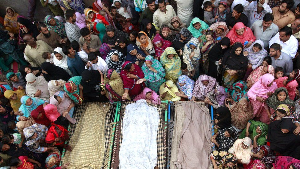 Muslim women and men gathered around three bodies in 2014
