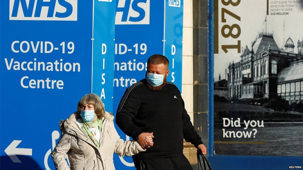 Elderly woman being escorted by younger man both in face masks to vaccination centre in converted Winter Gardens in Blackpool