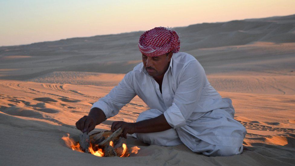 File picture of desert safari driver building a small fire to make mint tea before sunset during a trek through the Great Sand Sea outside the Egyptian oasis of Siwa
