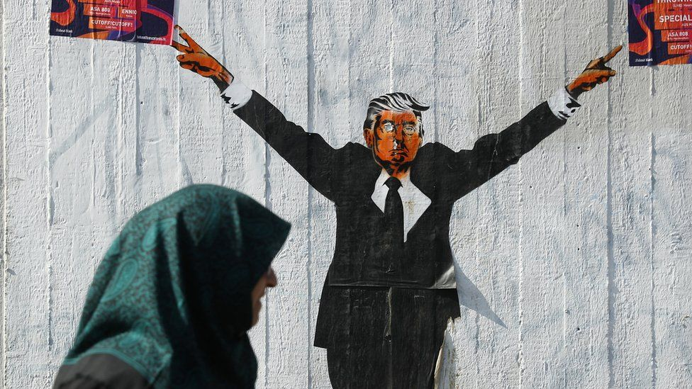 A Muslim woman walks past a street artist's rendition of U.S. President Donald Trump on 27 June, 2017 in Berlin, Germany