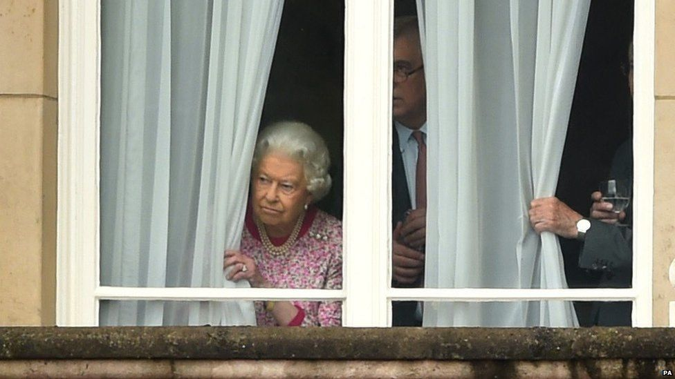 The Queen peers out of the window at Buckingham Palace