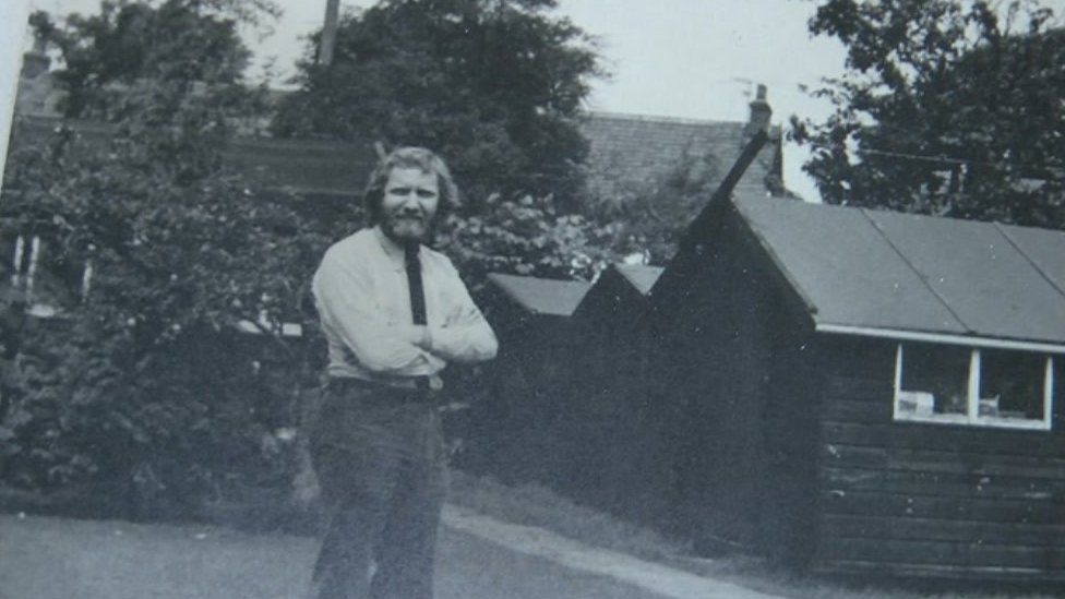 Kip Bertram next to one of the sheds where he started Bertram Books