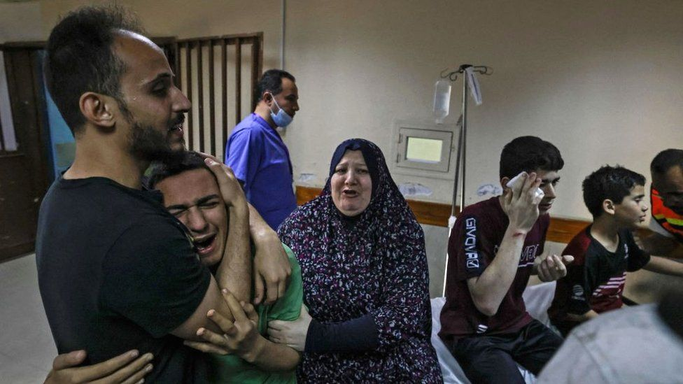 A member of the Abu Dayer family, surrounded by relatives, cries at the Al-Shifa hospital after the death of his father and cousin in an Israeli air strike