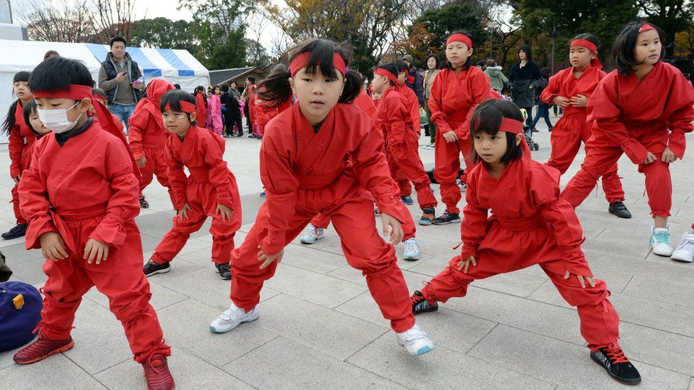 Children in ninja costume warming up for a ninja-themed dance performance in Iga, Mie prefecture