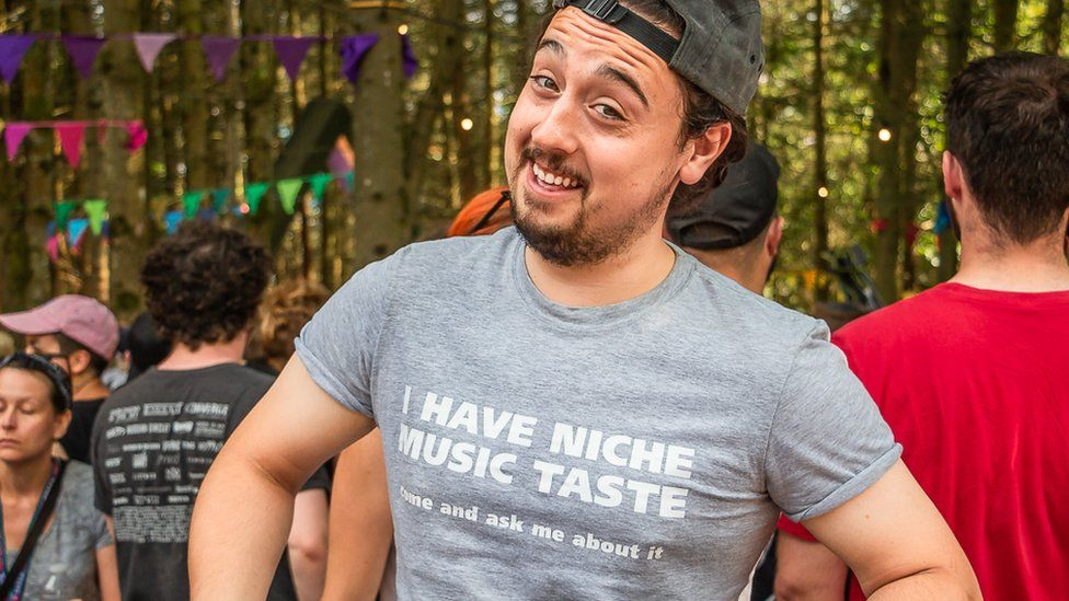 """A man wearing a t-shirt that says """"I have niche music taste come and ask me about it"""""""