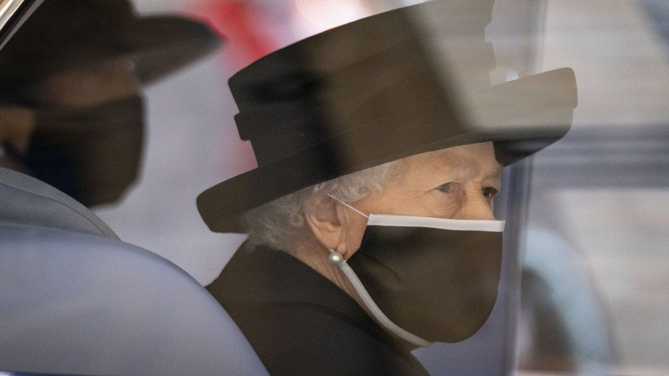 The Queen dressed in black with a black face mask
