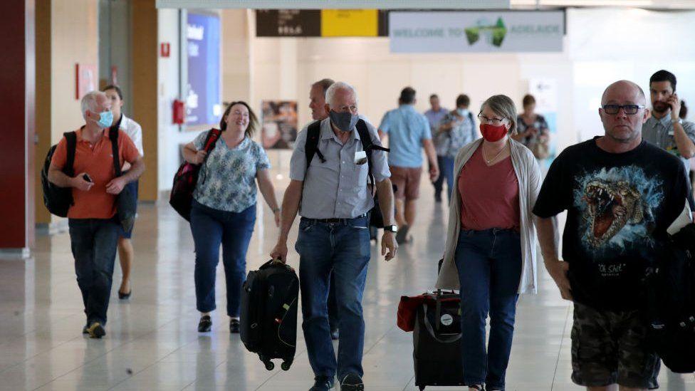 Passengers wearing masks walk through Adelaide Airport