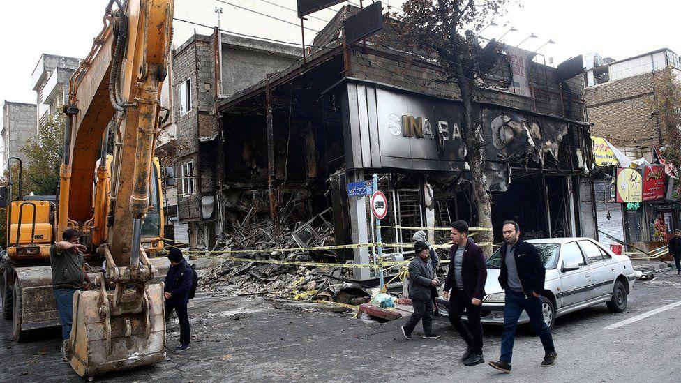 File photo showing people walking past a burned bank in Tehran, Iran (20 November 2019)