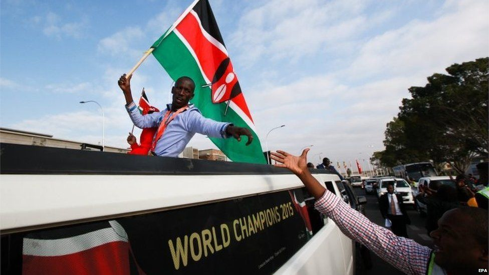 Kenyan Ezekiel Kemboi (L), who won gold medal in men's 3,000 metres Steeplechase final during the Beijing 2015 IAAF World Championships greets people upon his arrival at the Jomo Kenyatta Internal Airport (JKIA) in Nairobi