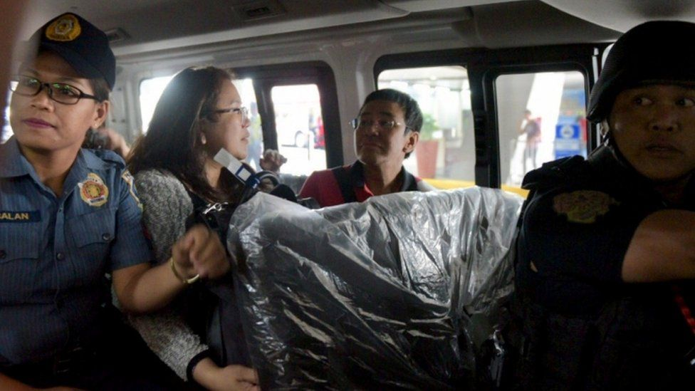 Maria Ressa being driven away in a police car on March 29