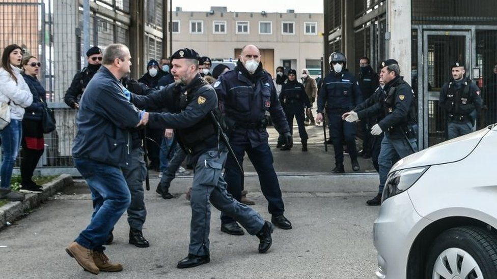 A man is restrained by a police officer outside a prison in Modena, Italy. Photo: 9 March 2020