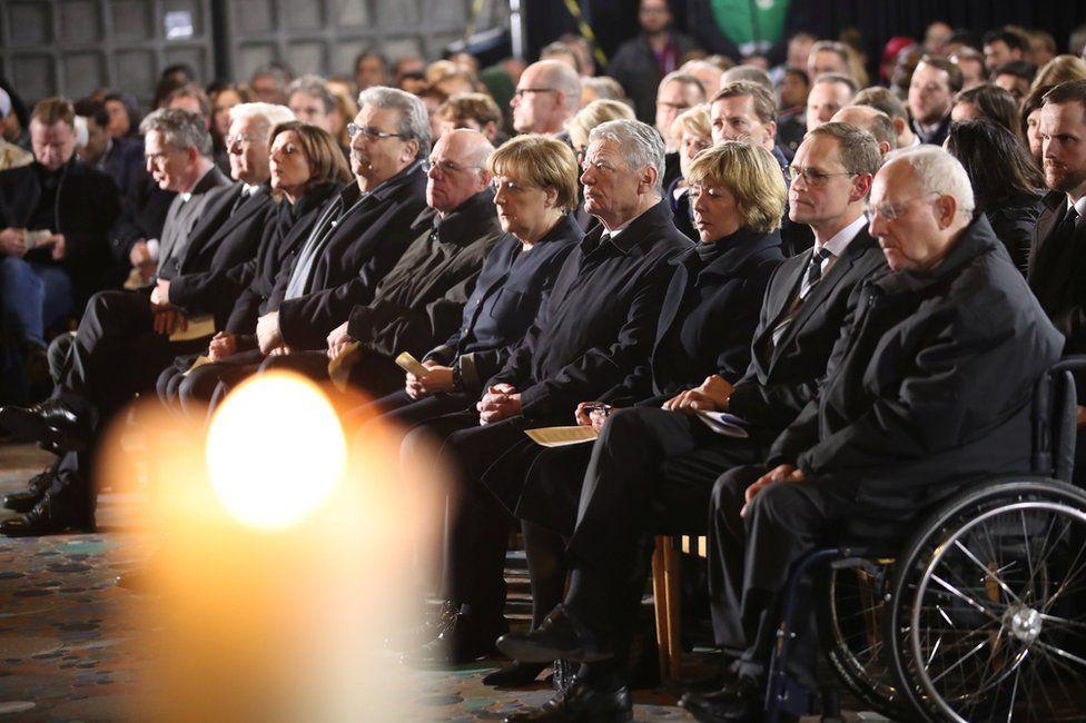 German Chancellor Angela Merkel (centre) and other politicians attend a commemoration in the Kaiser Wilhelm Memorial Church, Berlin, 20 December
