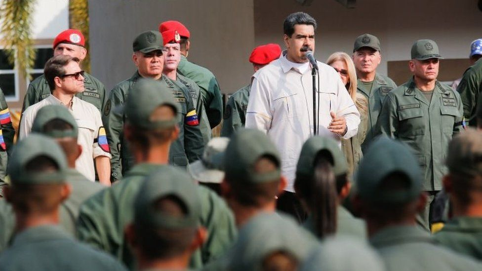Handout picture released by Miraflores Palace press office showing Venezuela's President Nicolas Maduro (C) delivering a speech next to Venezuelan Defence Minister Vladimir Padrino (2-L) during the march of loyalty with personnel of the Venezuelan Bolivarian National Armed Forces (FANB) in Carabobo state, Venezuela on May 21, 2019.