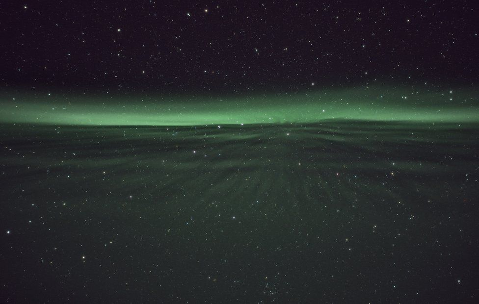 A shimmering green sheet reaches through a sky of stars towards a glowing green horizon
