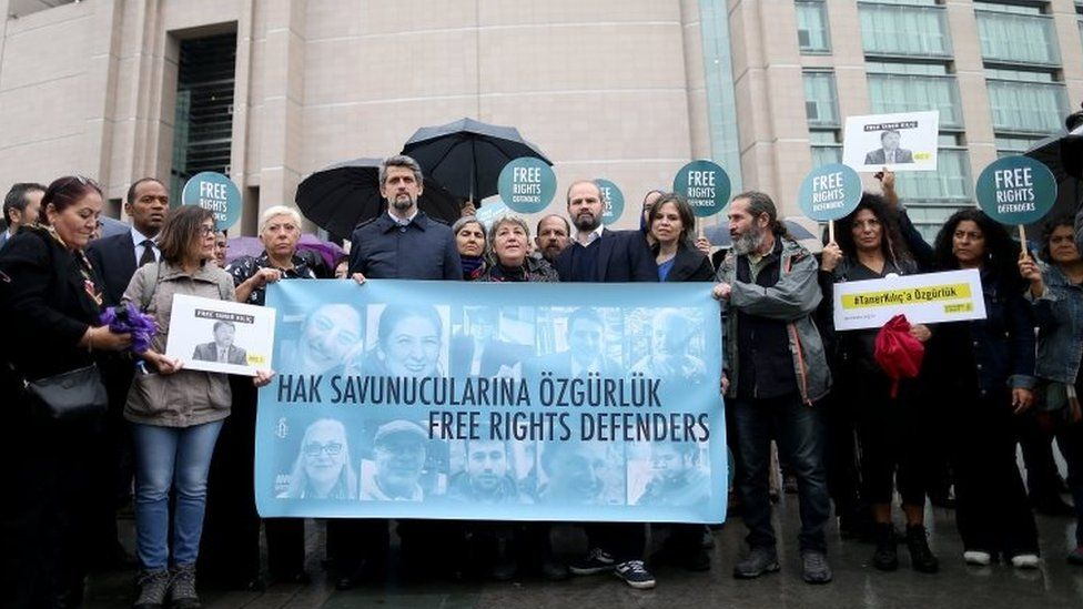People outside Istanbul's court hold placards and a banner with pictures of the accused activists. Photo: 25 October 2017