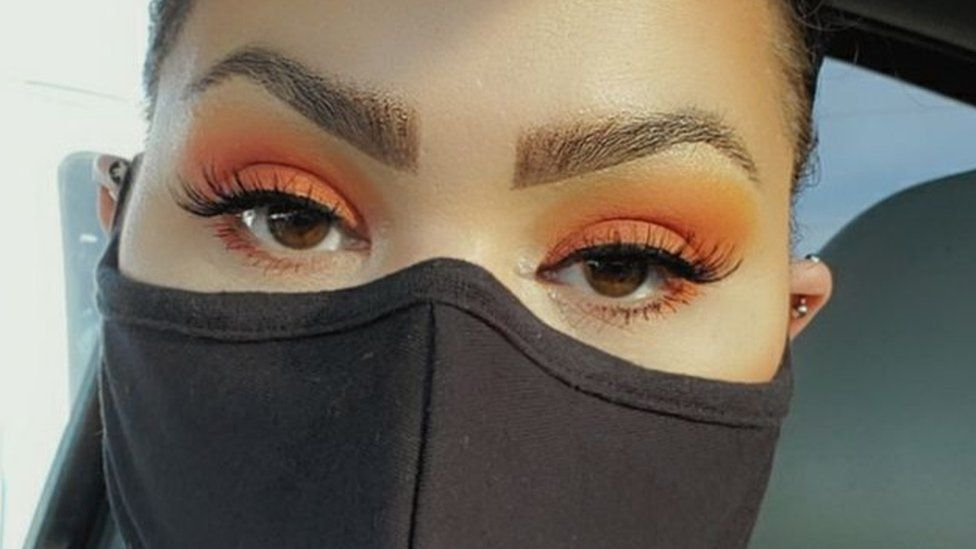 Melina Basnight wears a face mask and a strong eye makeup look, with orange shadow and long false lashes