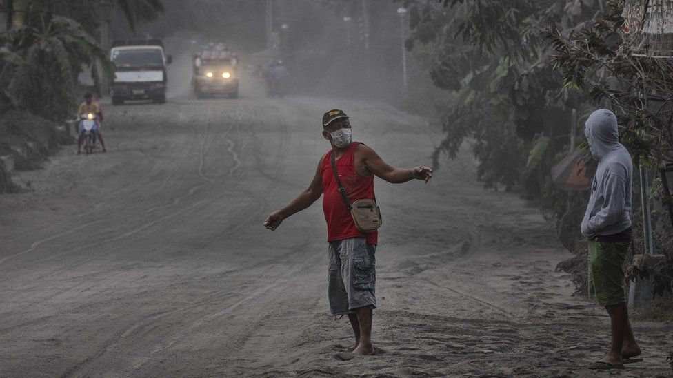Residents walk along a road covered in volcanic ash from Taal Volcano's eruption on January 13, 2020 in Lemery, Batangas province, Philippines