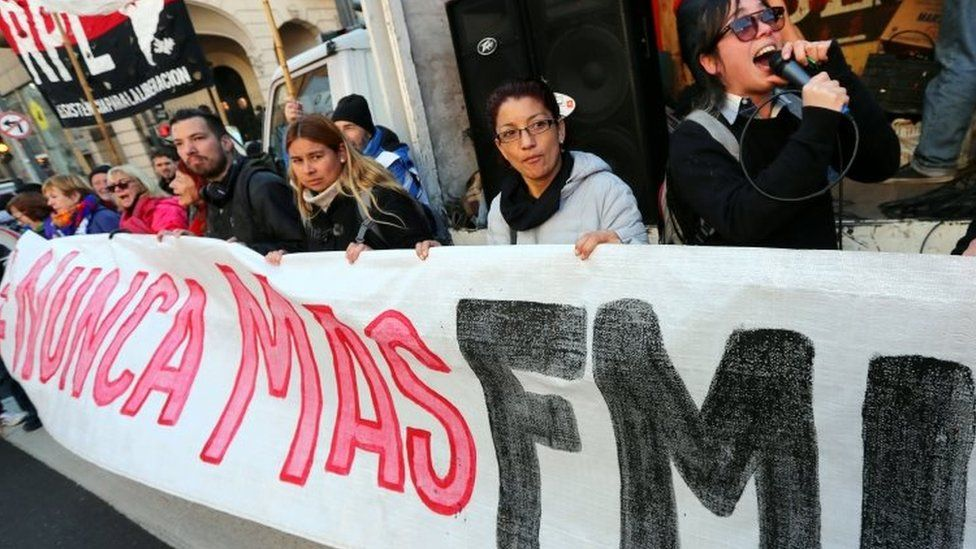 """Demonstrators hold a banner that reads """"IMF (International Monetary Fund), never again"""" during a protest against the G20 Meeting of Finance Ministers in Buenos Aires, Argentina, July 21, 2018."""