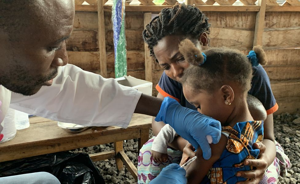 A handout photo made available by the World Health Organization (WHO) shows a child receiving a vaccination for measles at a health center in Goma