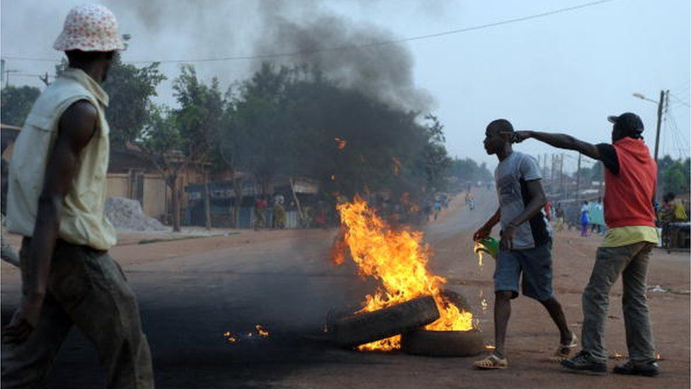 Opposition group members burn tyres on a road in Gagnoa on February 20, 2010.
