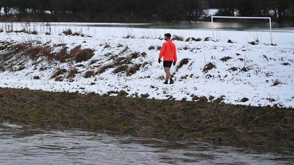 Man walks past River Mersey in Didsbury