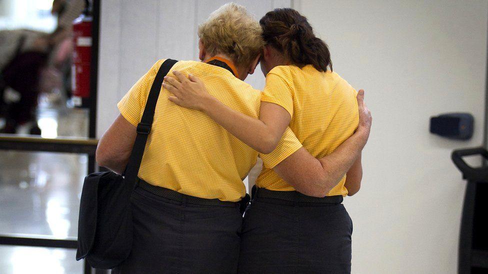 Two Thomas Cook staff members hug at Son Sant Joan airport in Palma de Majorca, 24 September 2019