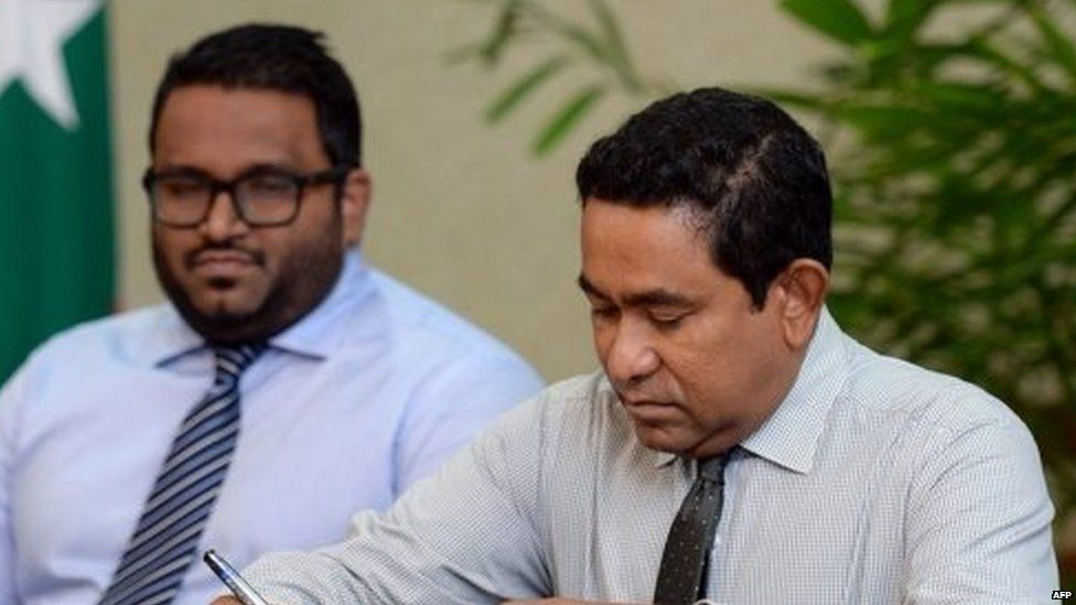 Maldivian President Abdulla Yameen (right) ratifies a land agreement as Vice President Ahmed Adeeb looks on (23 July 2015)