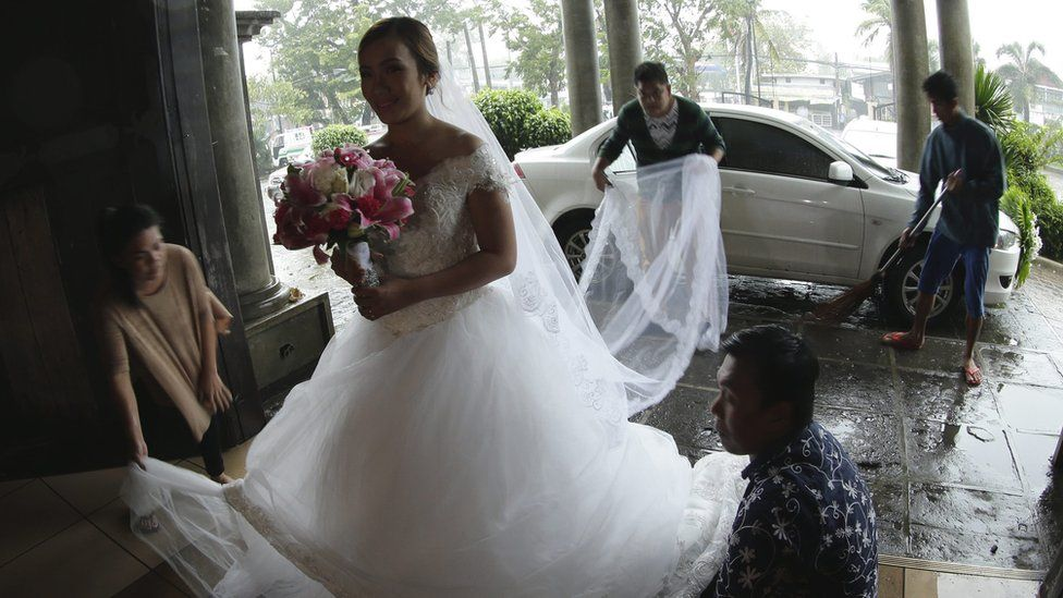 A bride arrives for her wedding in the Philippines despite the onset of Typhoon Koppu