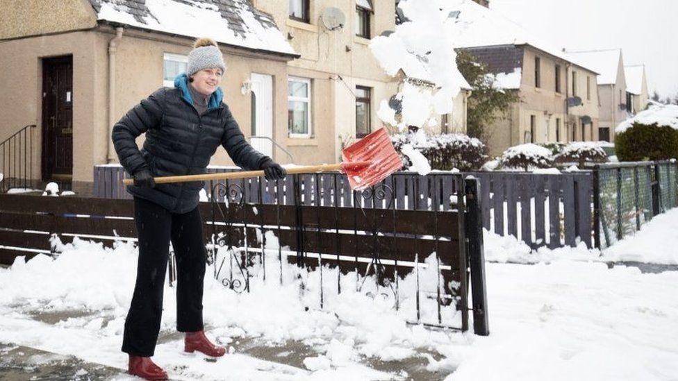 Kasia Wojcik clears snow from her driveway in Penicuik, Midlothian