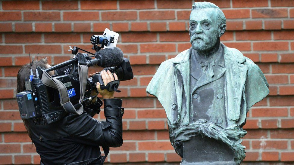 A woman films a statue of Swedish inventor of dynamite Alfred Nobel