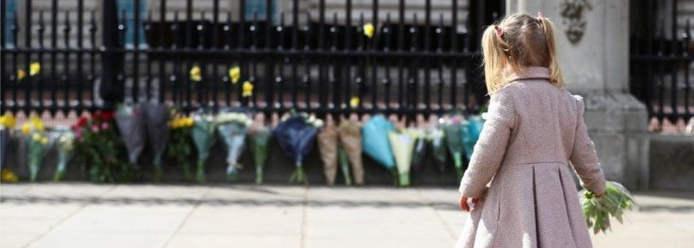 Maggie, 2, lays down a bouquet of flowers outside Buckingham Palace
