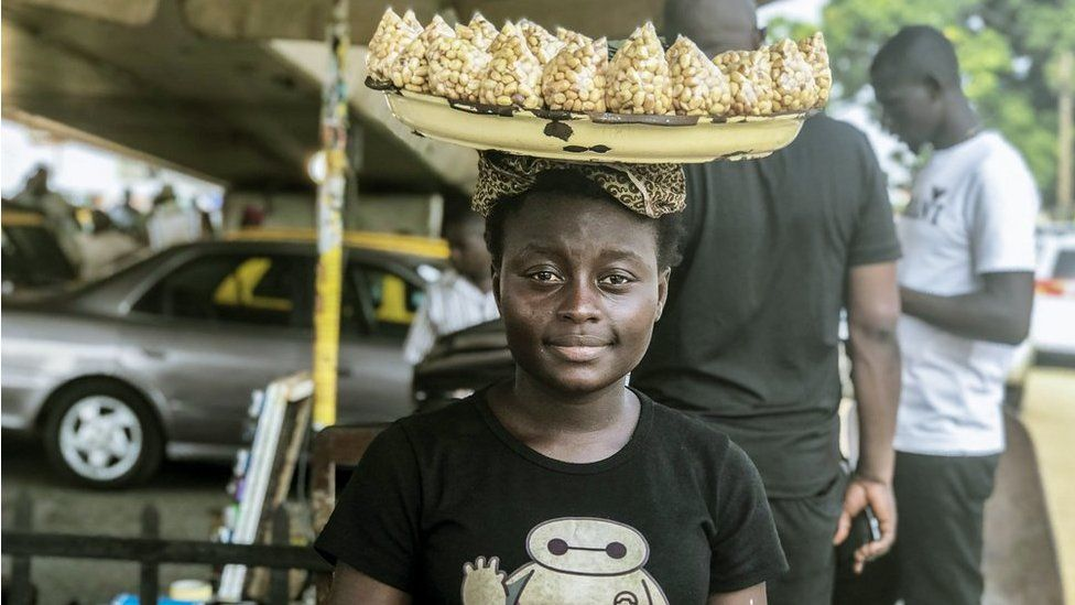 Street seller with a tray of groundnuts on her head