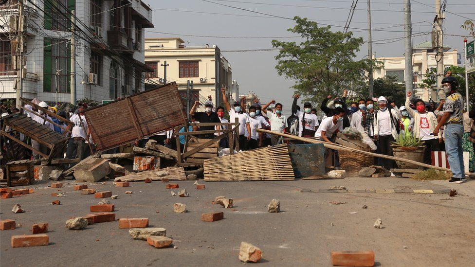 Demonstrators gesture at riot police behind makeshift barricades during a protest against the military coup in Mandalay