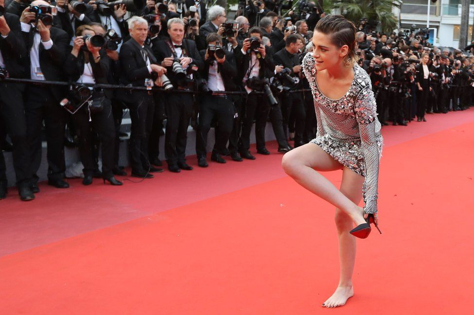 US actress and member of the Feature Film Jury Kristen Stewart removes her shoes on the red carpet as she arrives for the screening of the film BlacKkKlansman at the 71st edition of the Cannes Film Festival in Cannes, southern France. 14 May 2018.
