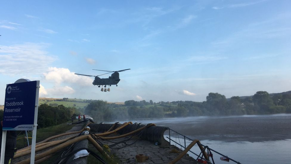 Helicopter flies over reservoir