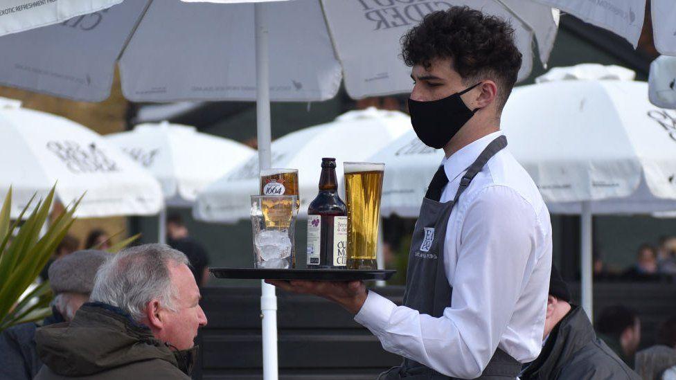 Waiter in mask serves drinks