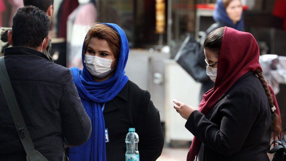 Women wearing face masks stand in a street in Tehran, Iran (26 February 2020)