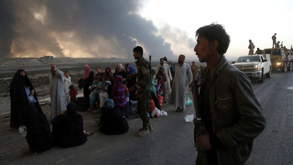 People flee their homes during fighting between Iraqi security forces and IS near Mosul, 18 October