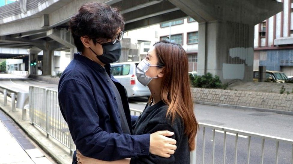 Pro-democracy activist Sam Cheung hugs his wife as he arrives to report to the police station