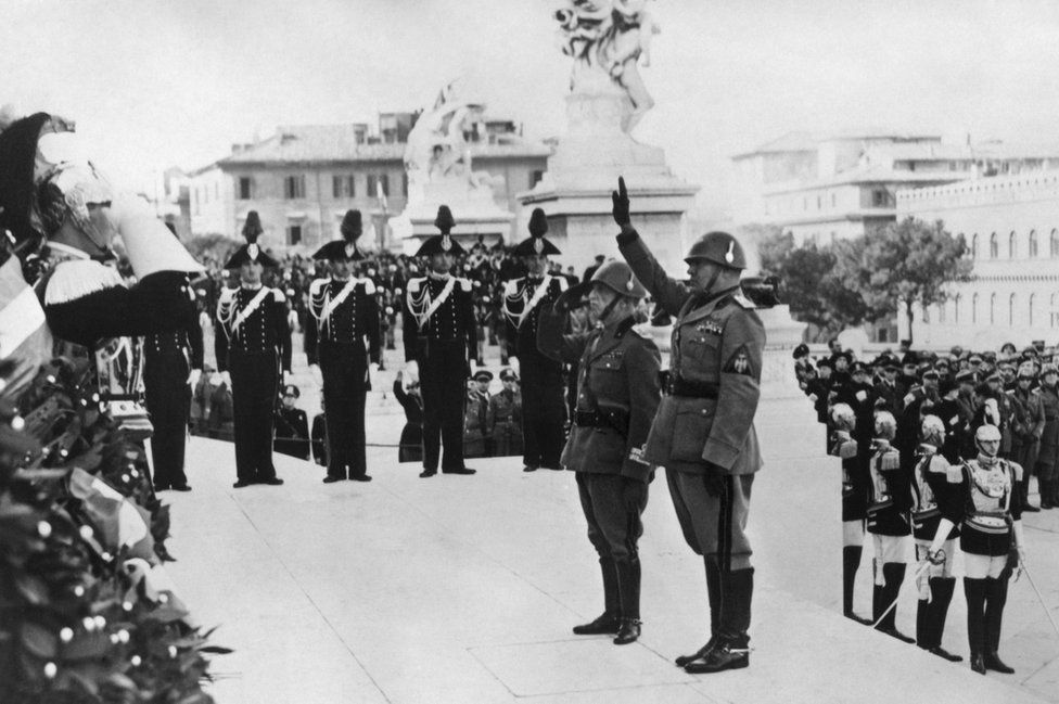 This file photo taken on 1 November 1938 shows Italian fascist dictator Benito Mussolini (right) and King Victor Emmanuel III of Italy (left) during a ceremony at the Tomb of the Unknown soldier, to celebrate the Victory day, in Rome