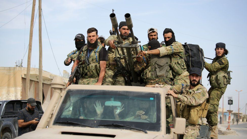 Syrian fighters advance on an armed military vehicle