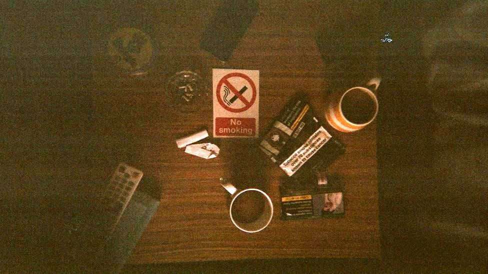 A birds-eye view of a table with mugs and cigarettes on it