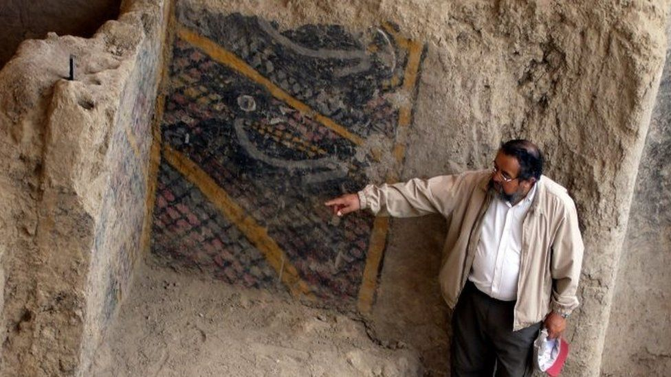 This handout file photo taken and released by Peruvian national news service Andina on November 10, 2007 shows Peruvian archaeologist Walter Alva pointing what is supposed to be the most ancient mural painting in America, in a temple in Chiclayo, more than 1000 kms north of Lima.