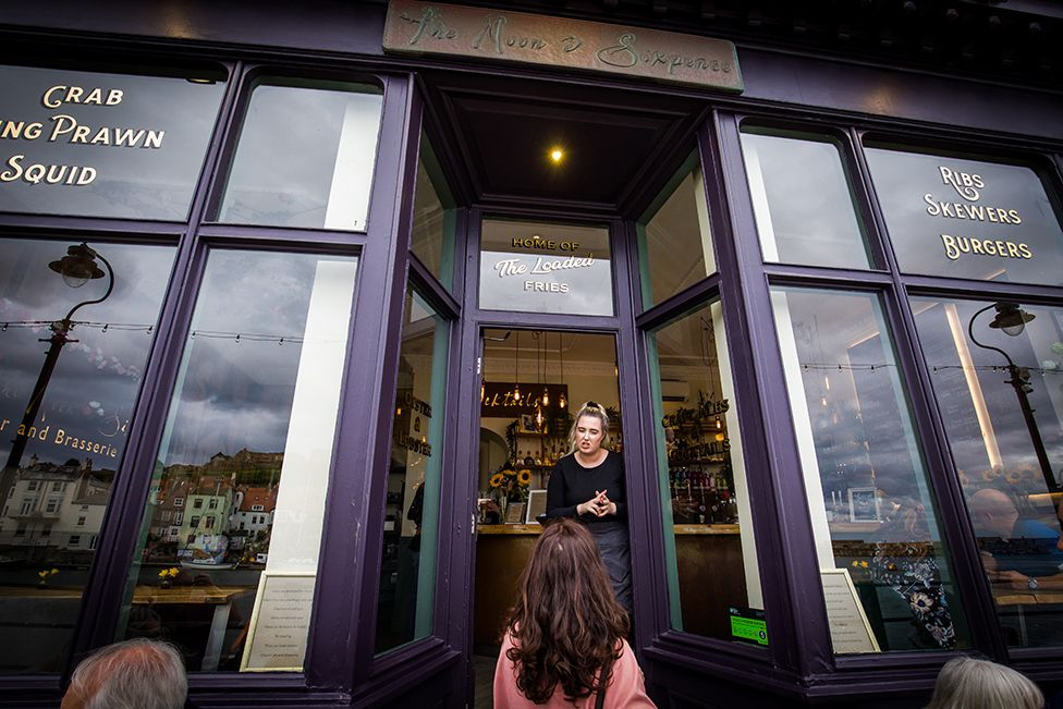 A member of staff telling people the bar is full at The Moon and Sixpence, Whitby