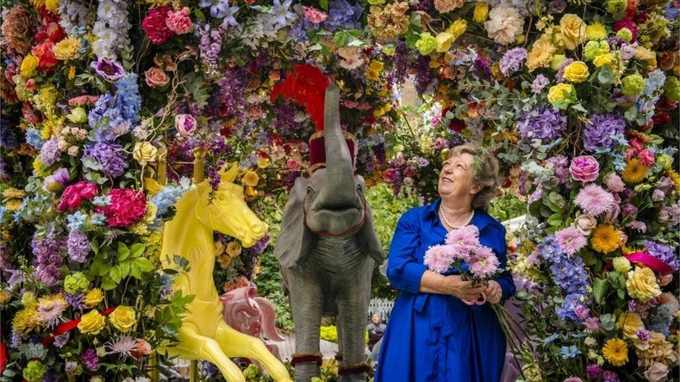 Florist Judith Blacklock puts the finishing touches to a floral carousel installation in Halkin Arcade, which she has designed with Neill Strain for the Belgravia in Bloom festival