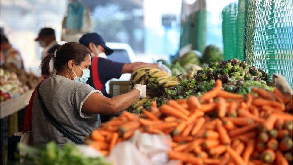 A woman wearing a protective mask picks vegetables in a street market during the nationwide quarantine in response to the spread of coronavirus disease (COVID-19) in Caracas, Venezuela March 31, 2020.