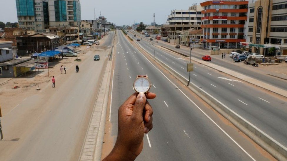 A watch showing the time at noon, is displayed for a photo as people walk past Ring Road Central Street, which is almost empty during the coronavirus disease (COVID-19) outbreak, in Accra, Ghana, March 31, 2020