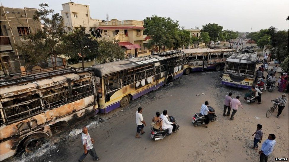Commuters move past damaged passenger buses which were burnt in the clashes between the police and protesters in Ahmedabad, India, August 26, 2015.