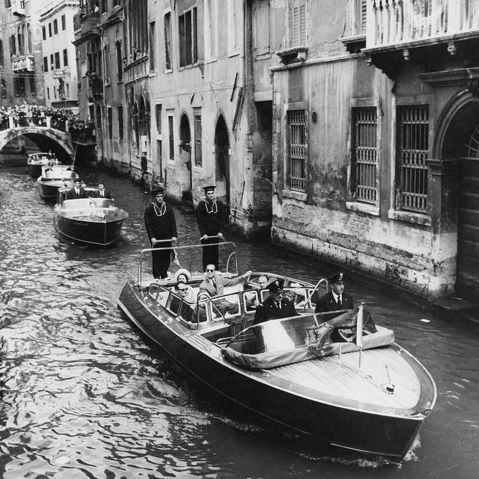 Queen Elizabeth II and Prince Philip, Duke of Edinburgh sit together in the rear seat of a motor boat as they take a cruise down a canal in Venice on the 3rd day of a State Visit to Italy on 4 May 1961.